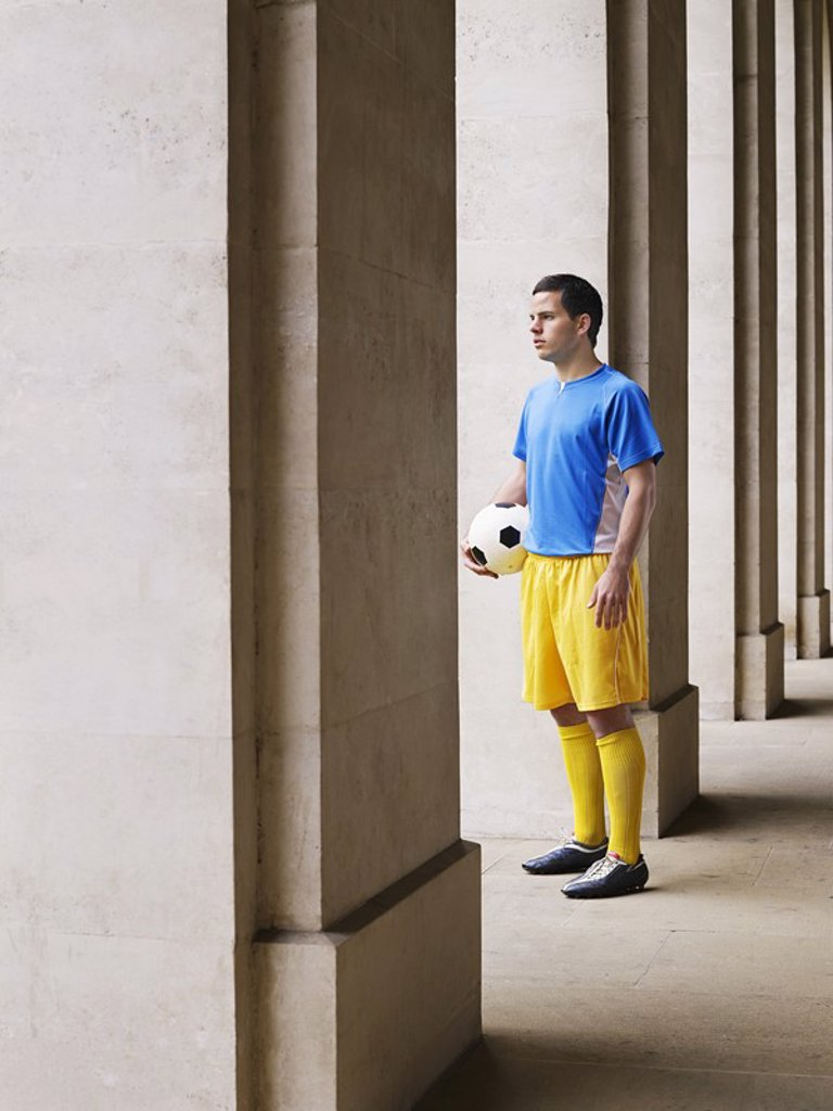 Soccer player holding ball standing in portico : Stock Photo