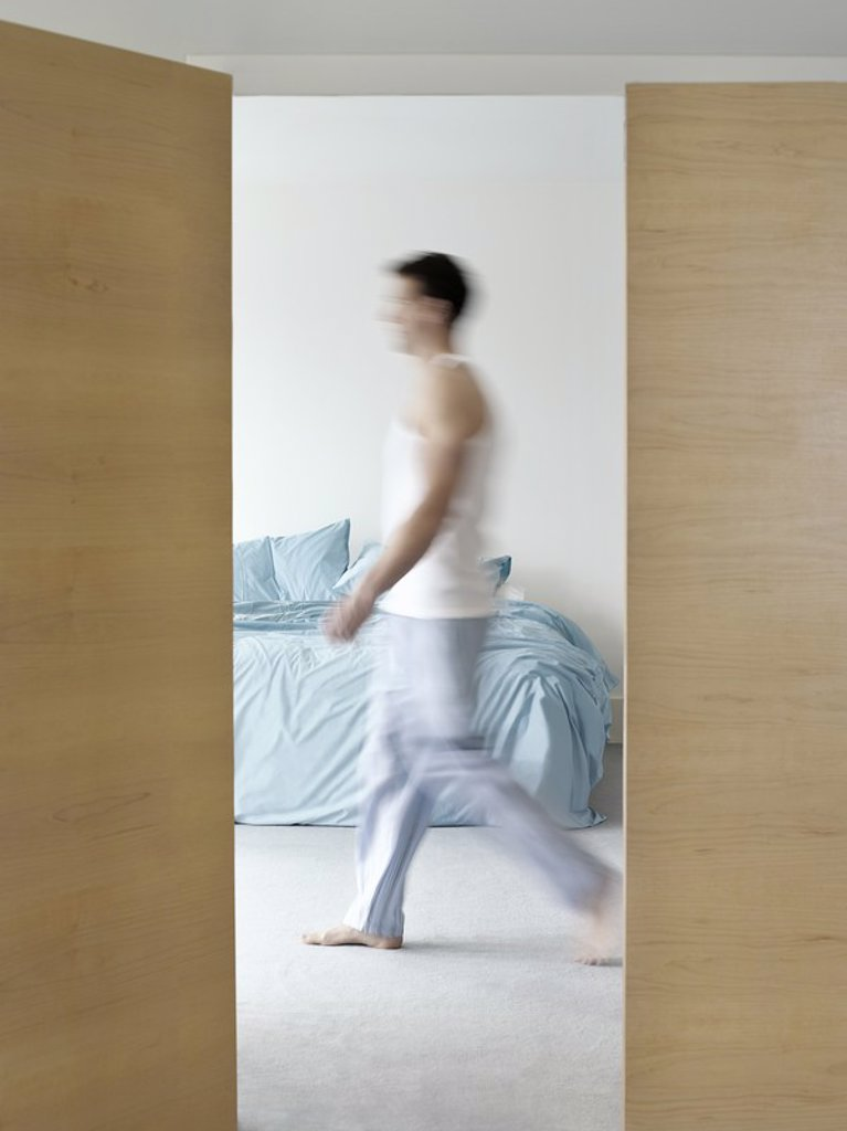 Man walking in bedroom side view blurred motion : Stock Photo