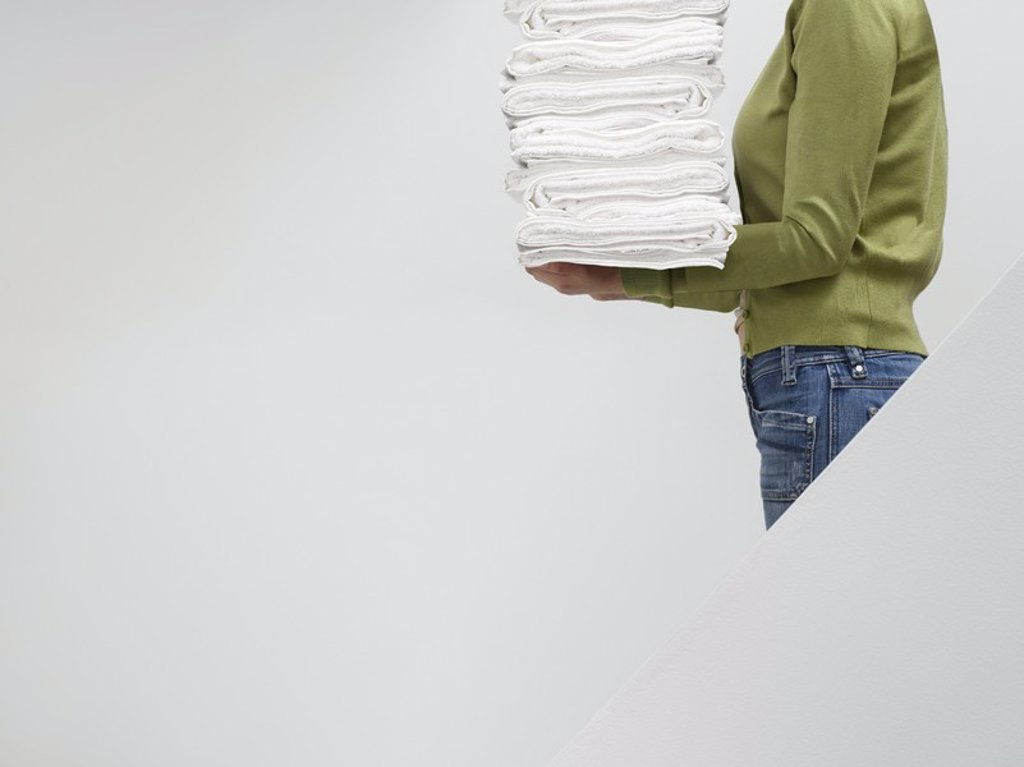 Stock Photo: 1654R-19646 Woman holding stack of fresh towels on stairs side view mid section