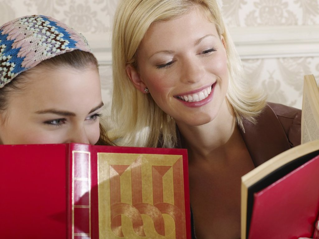 Two young women sitting on sofa holding books close up : Stock Photo