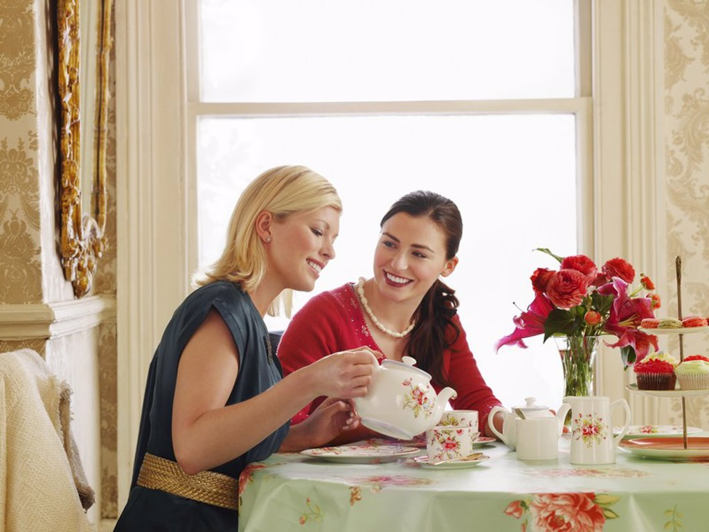 Two young women sitting at dining table pouring tea : Stock Photo