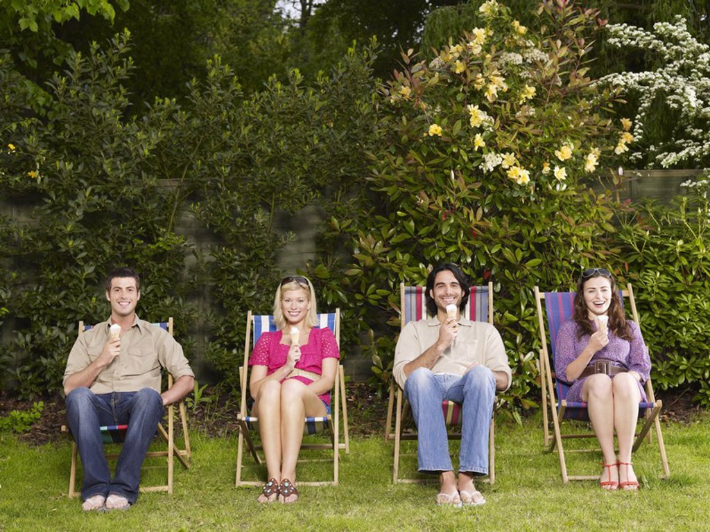 Group of young people sitting in row on deckchairs in garden eating ice creams : Stock Photo