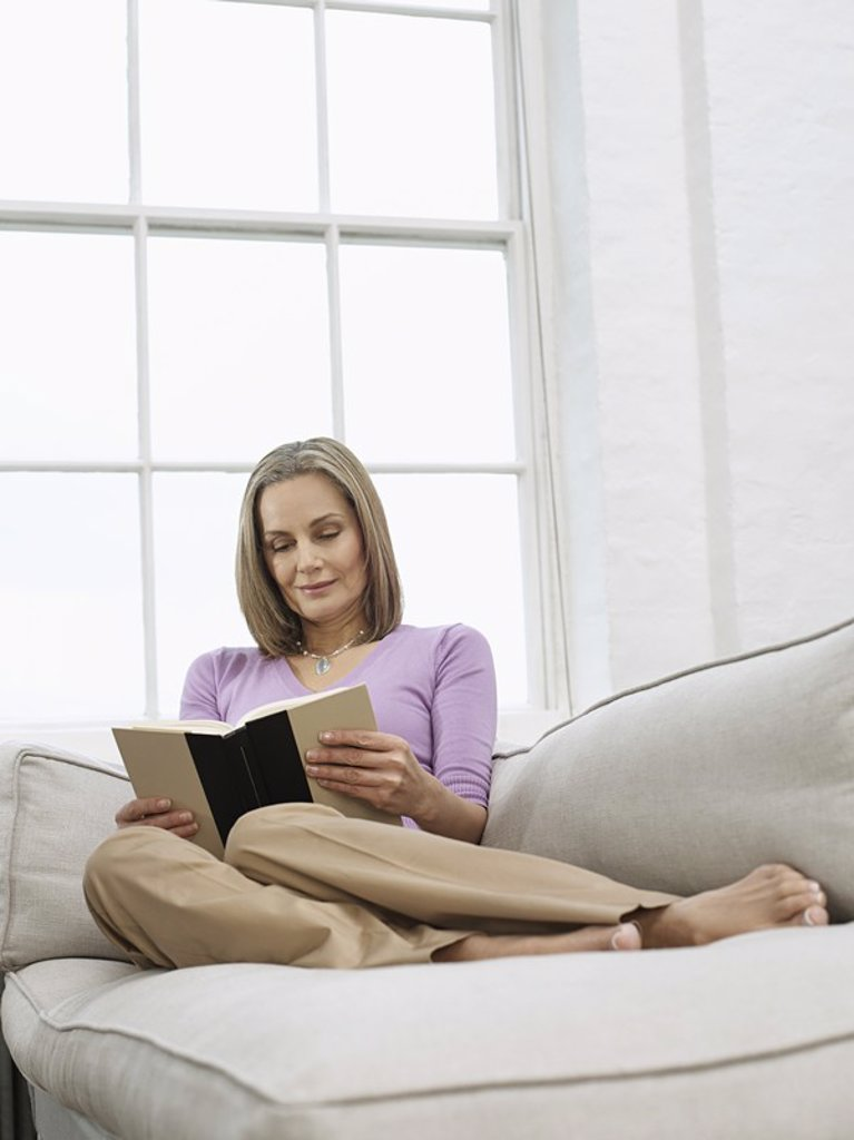 Mid adult woman reading book on sofa : Stock Photo