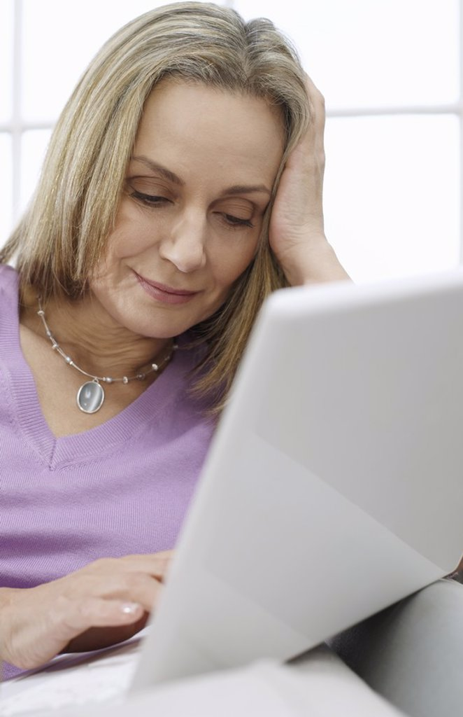 Mid_adult woman using laptop : Stock Photo