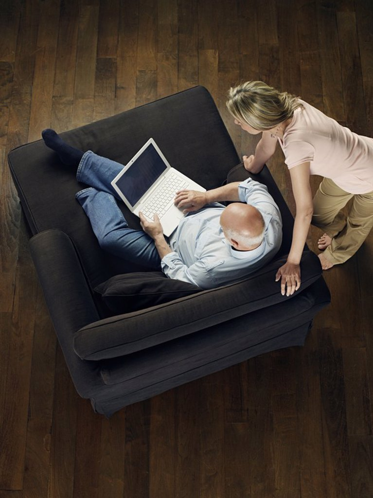 Middle_aged man sitting on sofa using laptop woman leaning and watching view from above : Stock Photo