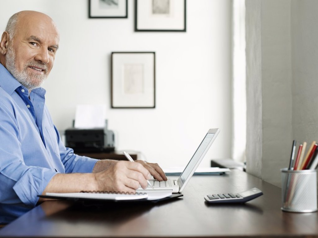 Stock Photo: 1654R-19738 Middle_aged man sitting at desk using laptop and writing in notepad