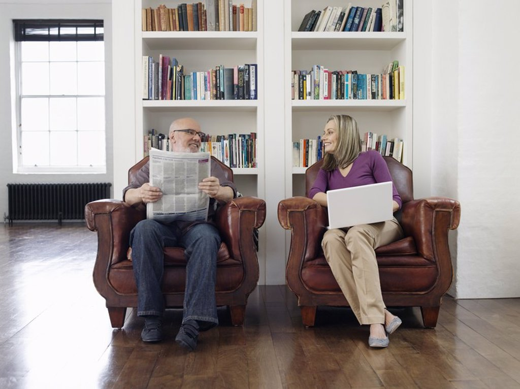 Couple sitting in armchairs man reading newspaper woman using laptop : Stock Photo