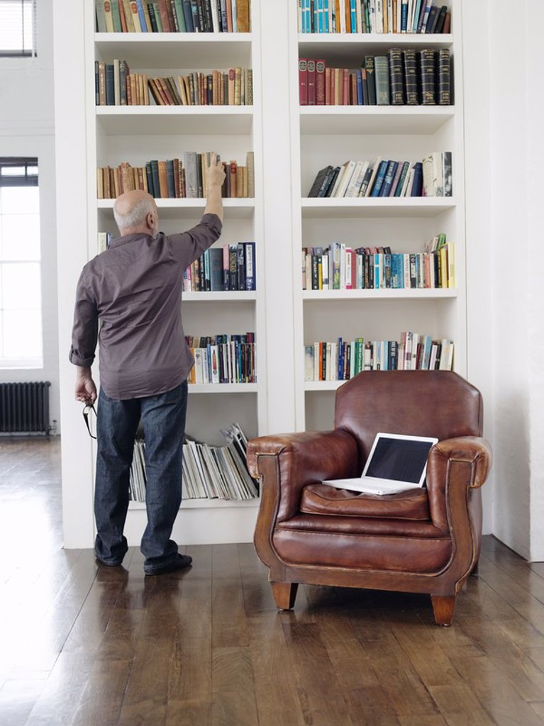 Middle_aged man taking book from shelf back view : Stock Photo