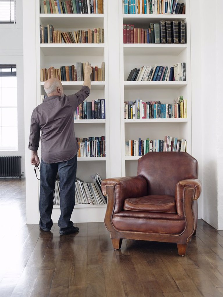 Stock Photo: 1654R-19745 Middle_aged man taking book from shelf back view