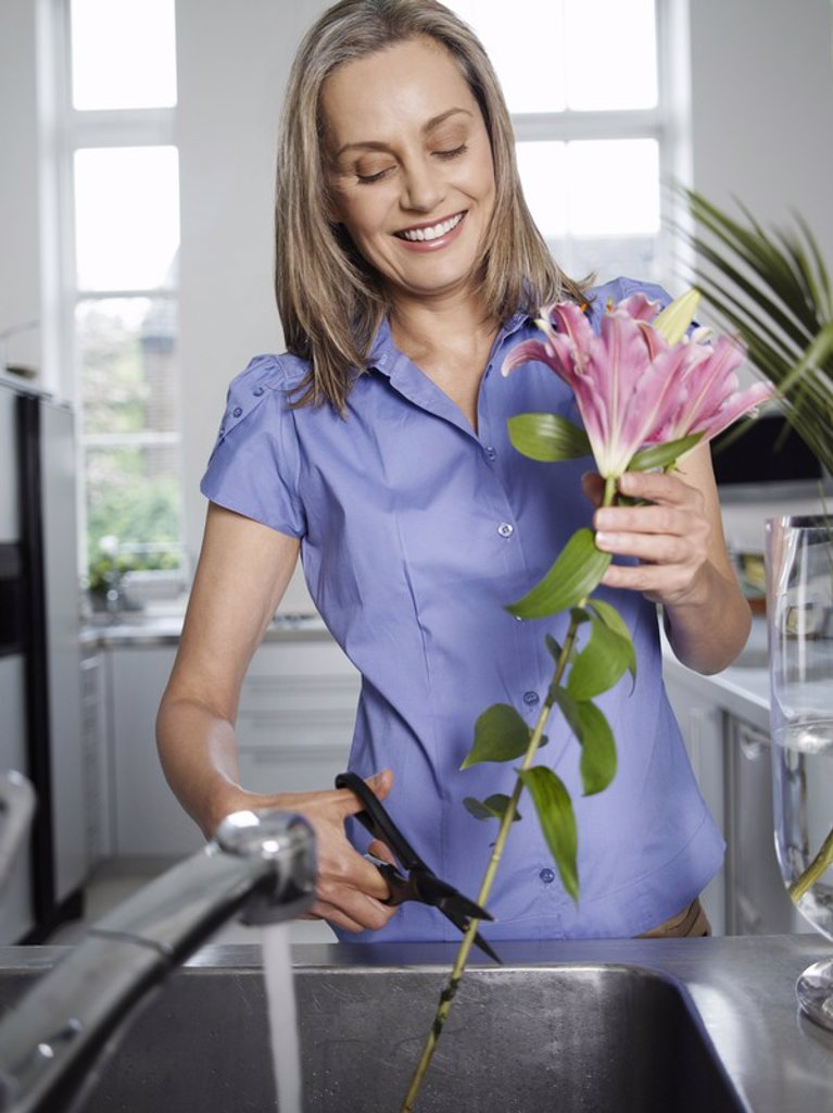 Mid_adult woman rinsing and cutting flowers in kitchen sink : Stock Photo