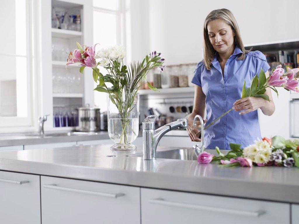 Stock Photo: 1654R-19751 Mid_adult woman at kitchen sink preparing flowers to be put in vase