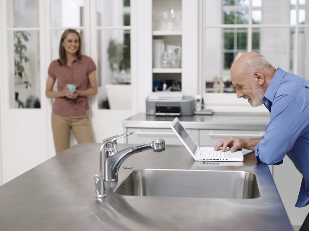 Man using laptop by kitchen sink woman watching from distance : Stock Photo
