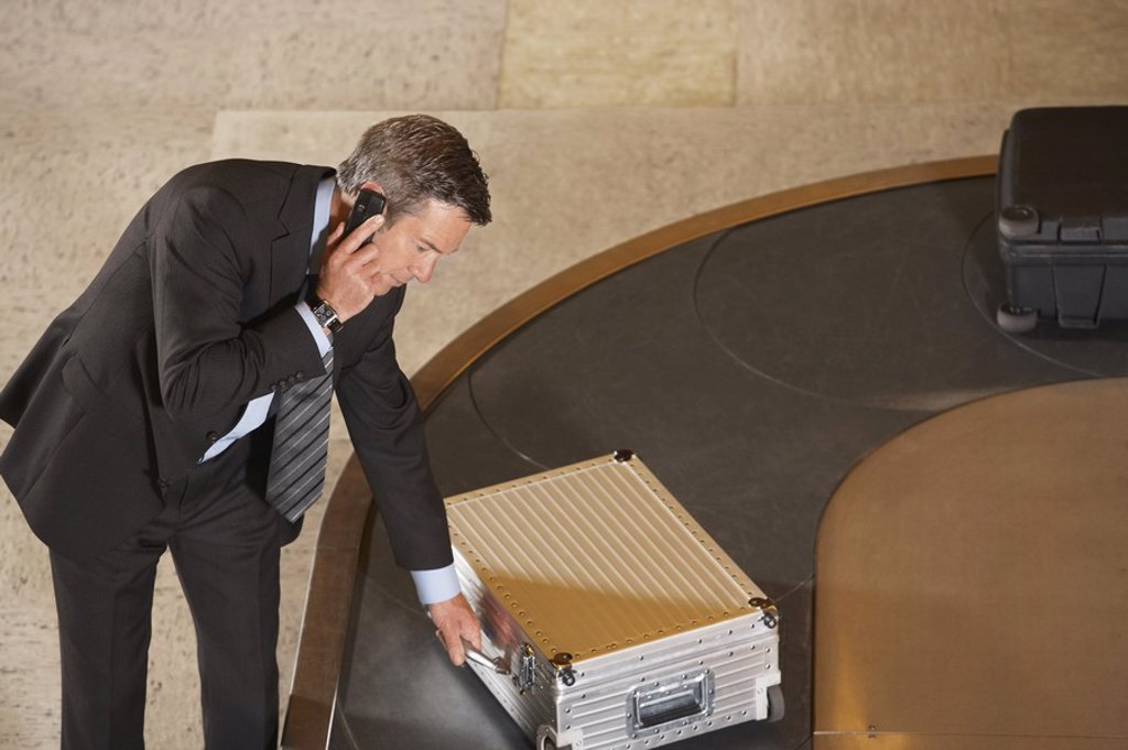 Business man claiming suitcase at luggage carousel in airport : Stock Photo