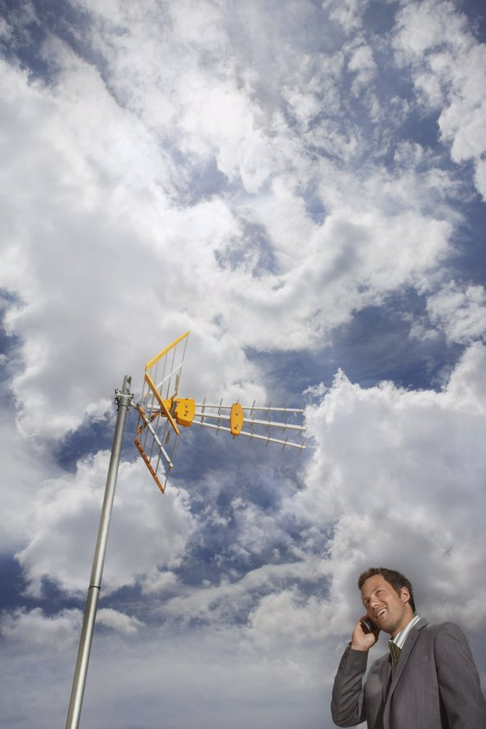 Business man using cell phone underneath satellite tower : Stock Photo