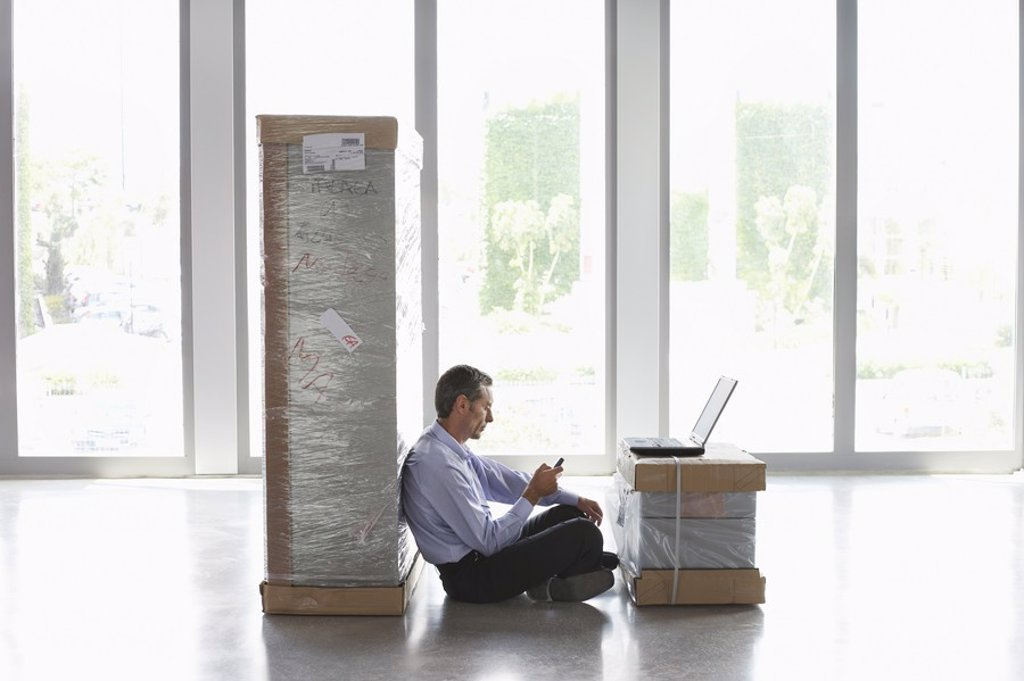 Man using mobile phone and laptop between packages in empty office : Stock Photo