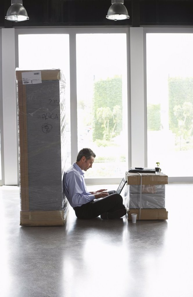 Man using laptop between packages in empty office : Stock Photo
