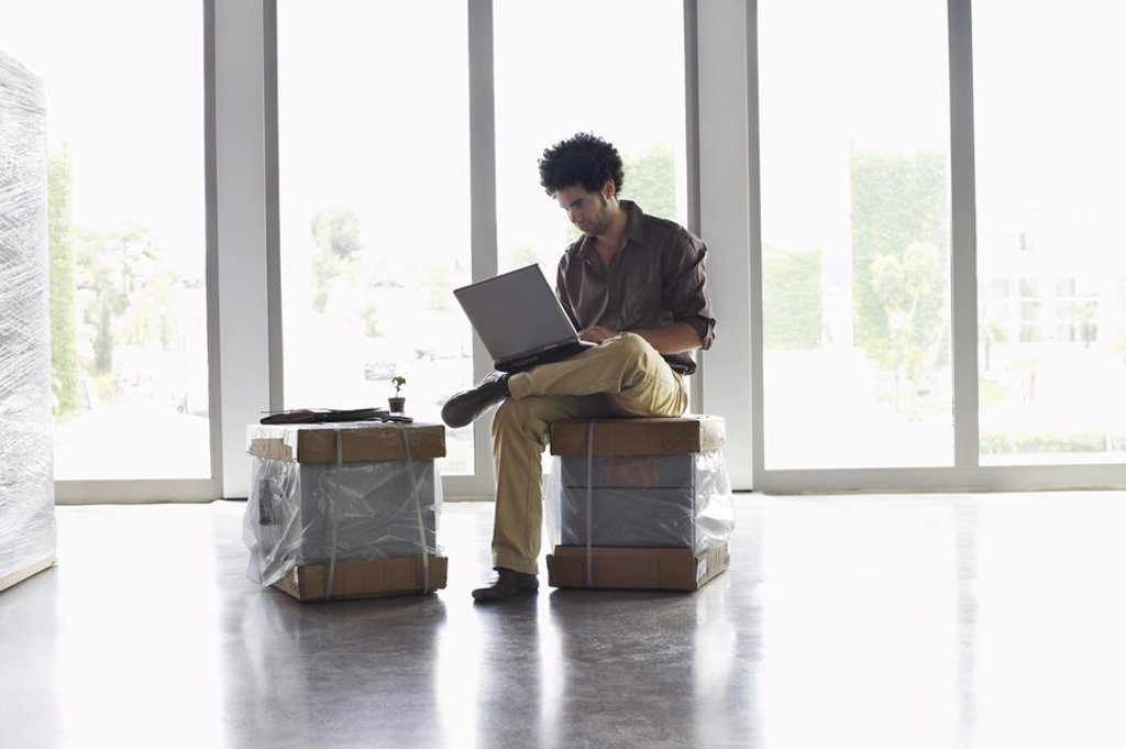 Stock Photo: 1654R-19931 Young man using laptop sitting on packages in empty office