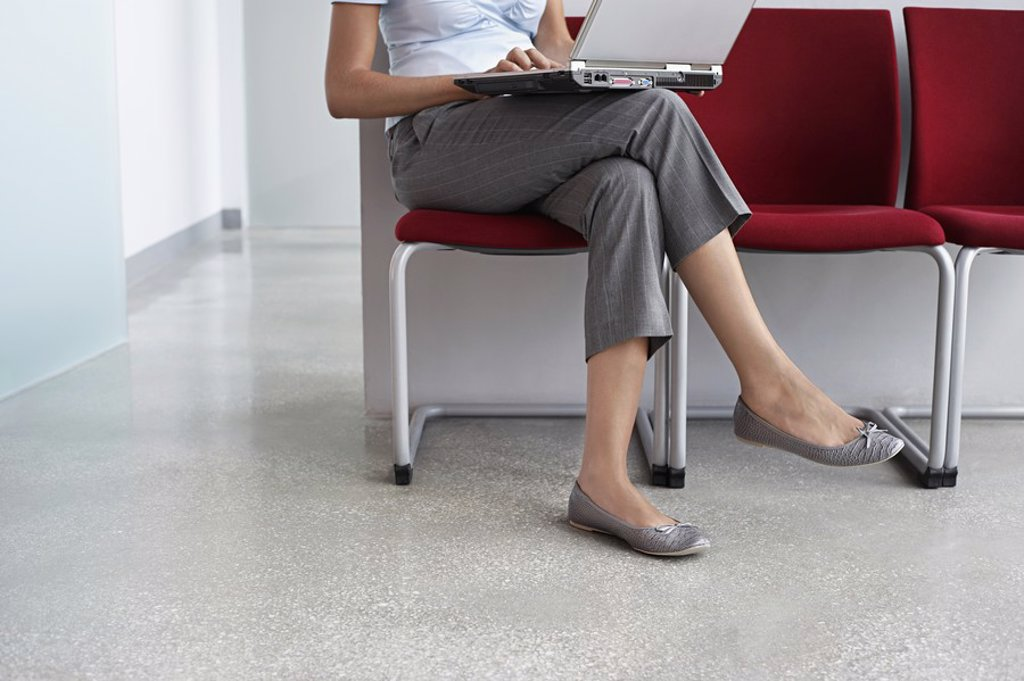 Stock Photo: 1654R-19944 Woman using laptop on chairs in corridor low section
