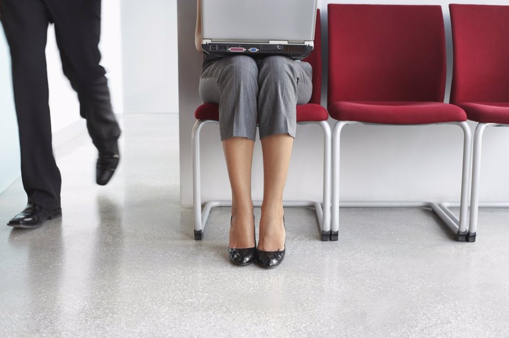 Stock Photo: 1654R-19946 Man walking past woman using laptop on chairs in corridor low section