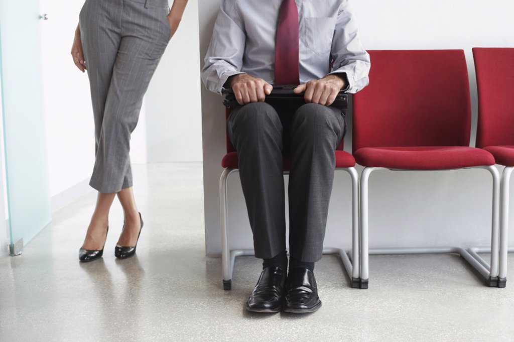 Woman standing beside man on chairs in corridor : Stock Photo
