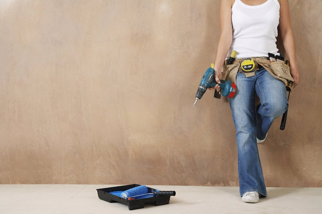 Woman with toolbelt and drill leaning against wall low section : Stock Photo