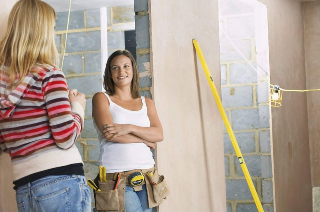 Woman with toolbelt leaning against wall taling to friend : Stock Photo
