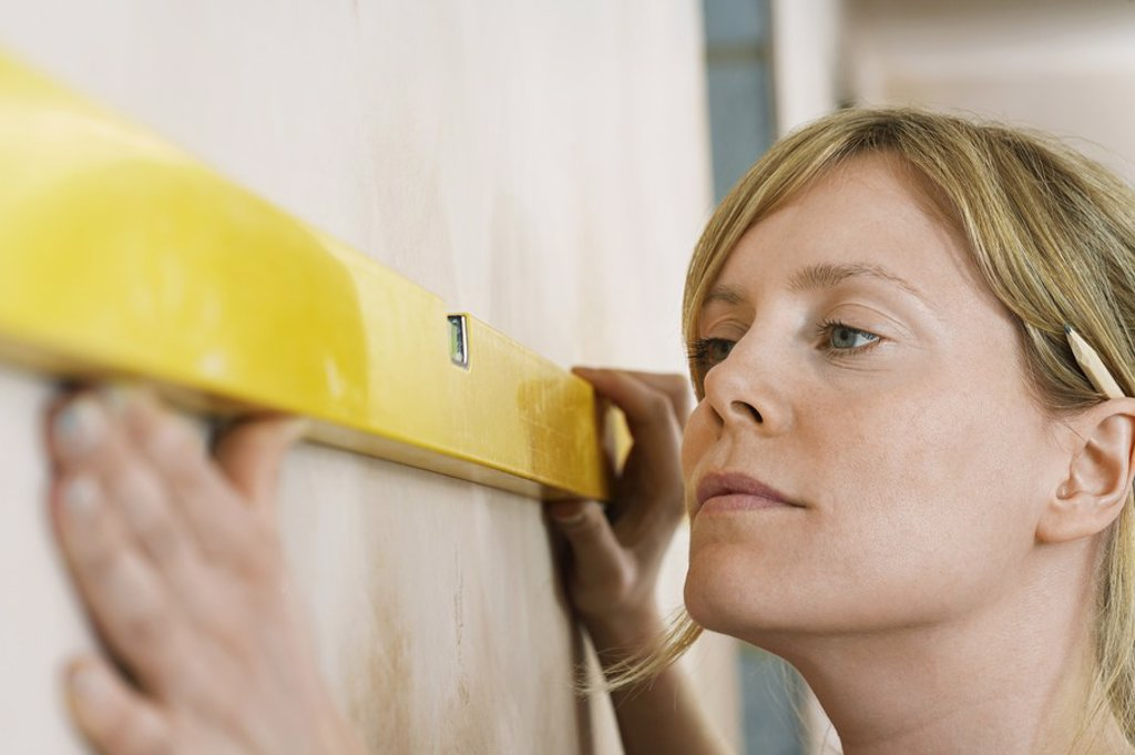 Stock Photo: 1654R-20063 Woman using spirit level close_up
