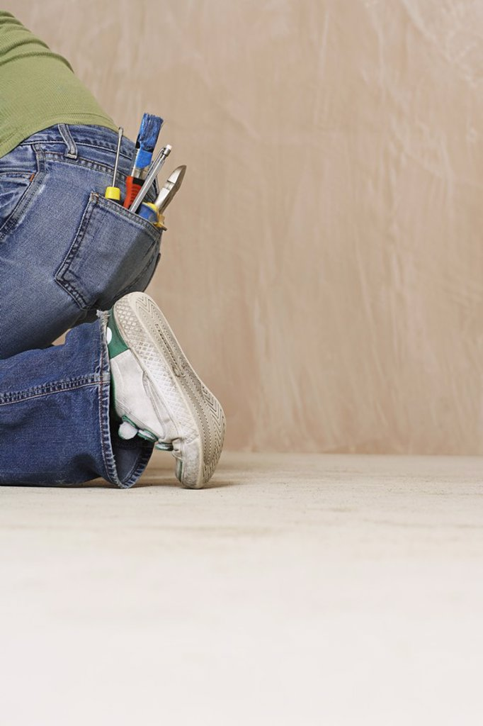 Stock Photo: 1654R-20075 Woman with paintbrush and hand tools in back jeans pocket kneeling on floor low section