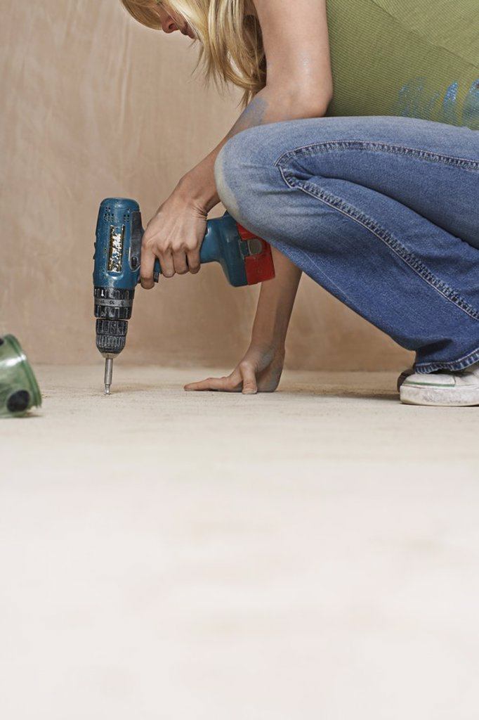 Woman drilling floor low section : Stock Photo