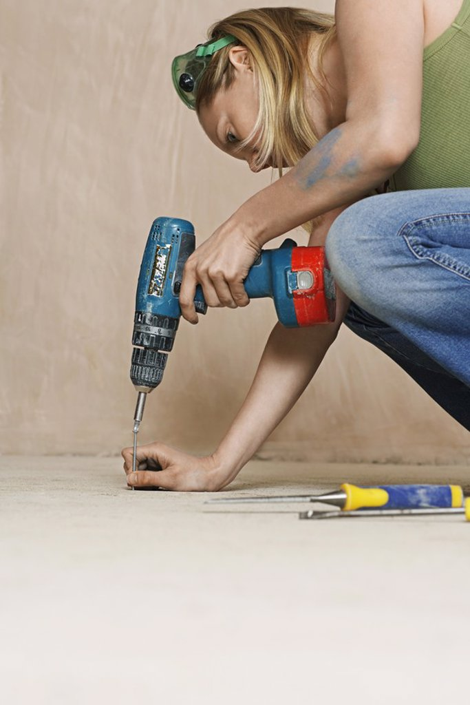 Woman drilling floor close_up : Stock Photo