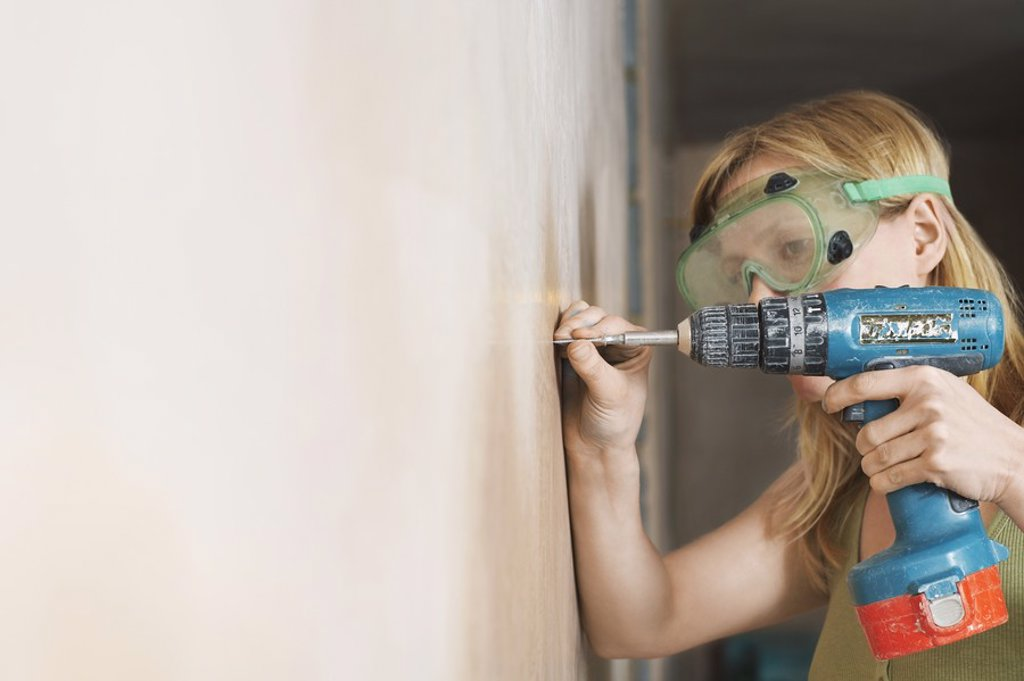Woman wearing protective goggles drilling wall close_up : Stock Photo