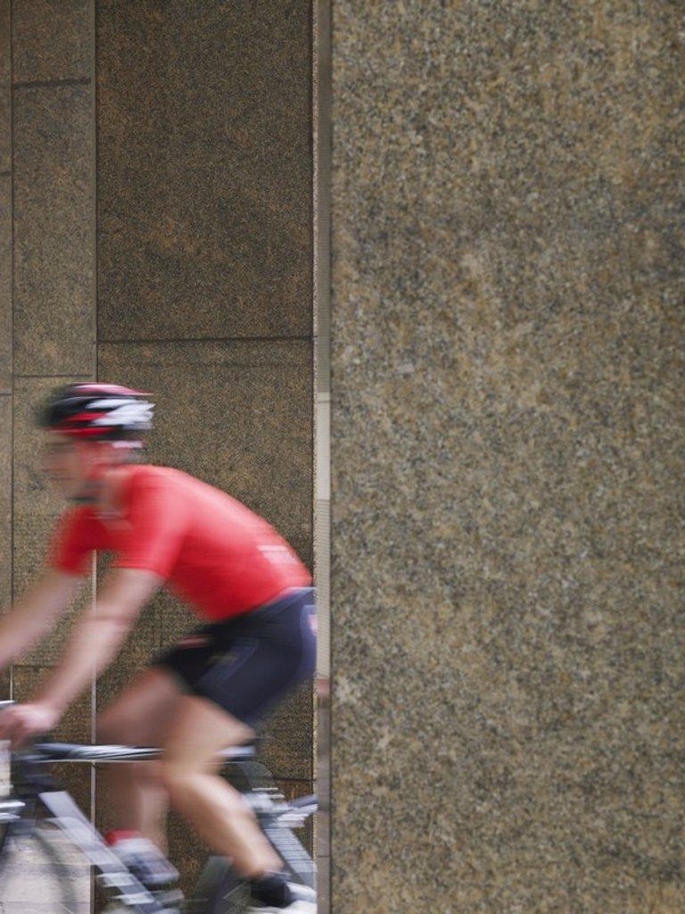 Man cycling between pillars motion blur : Stock Photo