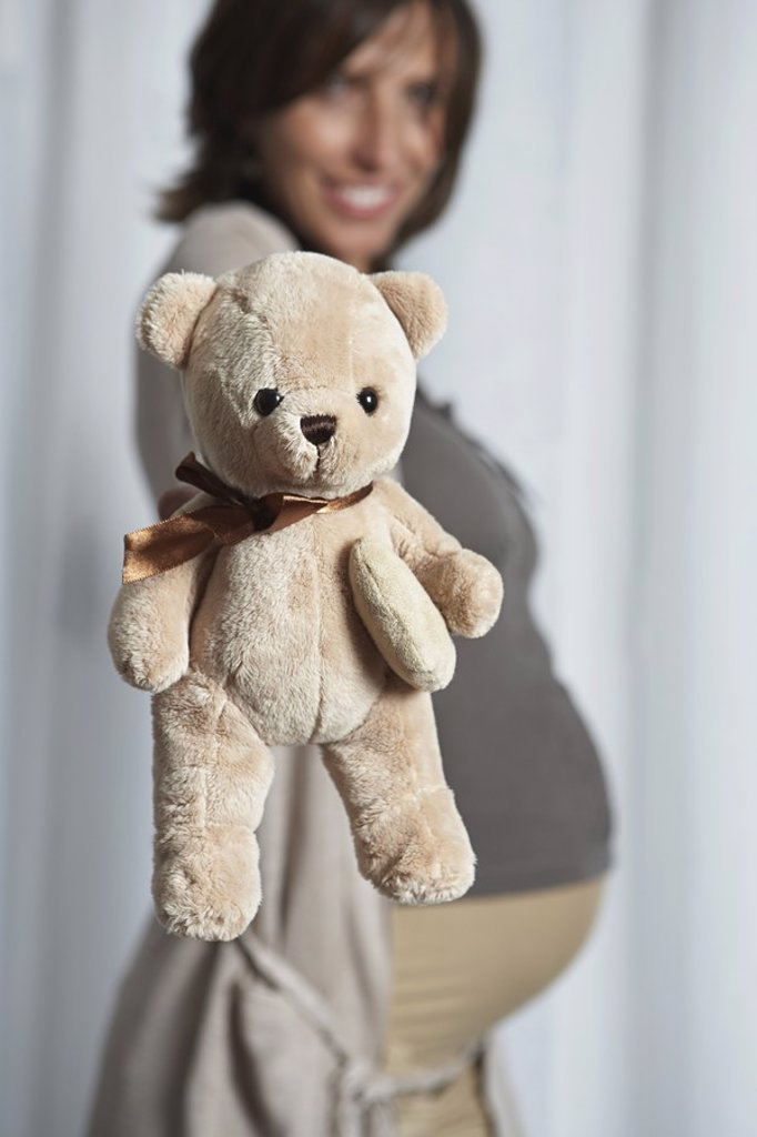 Pregnant woman holding up teddy bear indoors : Stock Photo