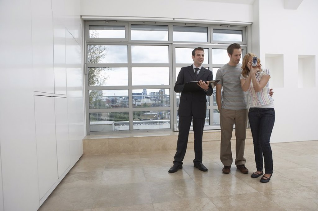 Real estate agent showing couple new apartment : Stock Photo