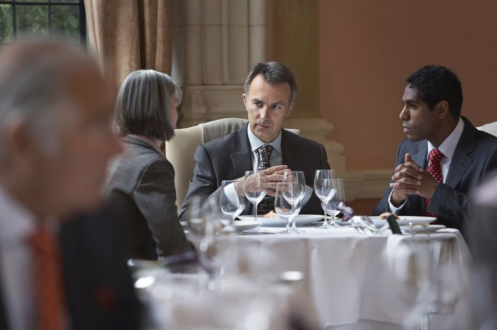 Three business people sitting at restaurant table talking : Stock Photo
