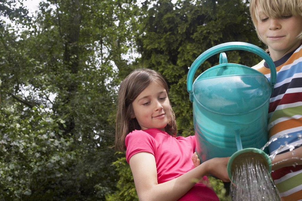 Stock Photo: 1654R-20446 Boy and girl 7_9 watering garden together