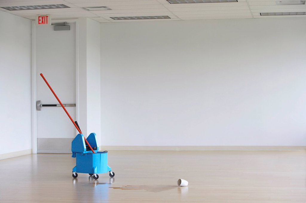 Stock Photo: 1654R-20865 Mop in pail by spilled coffee mug in empty room
