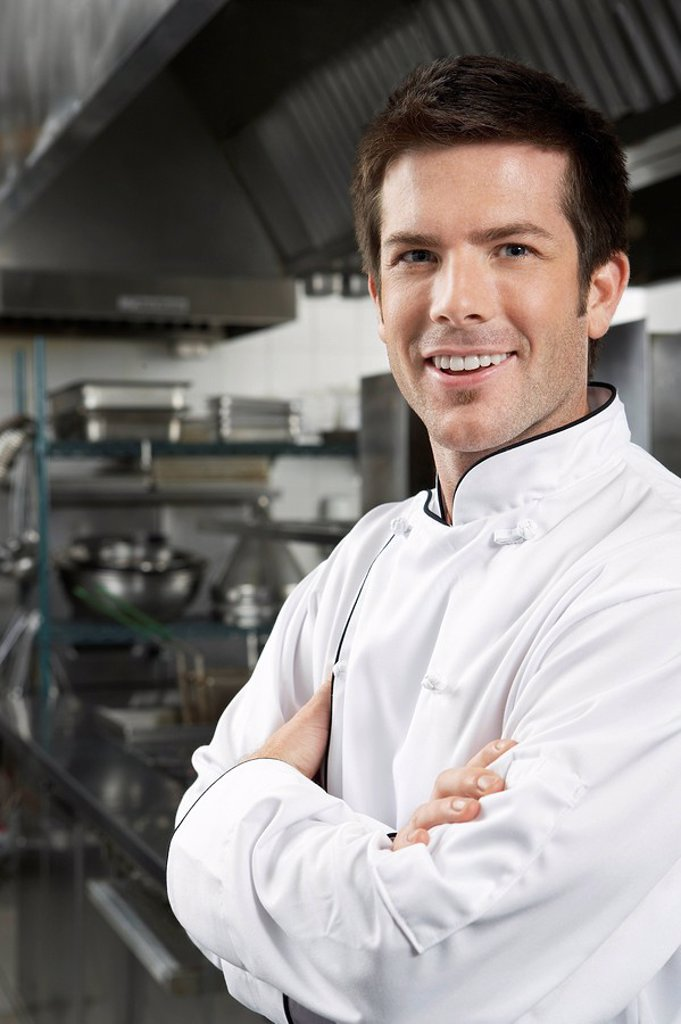 Male chef with arms crossed in kitchen portrait : Stock Photo