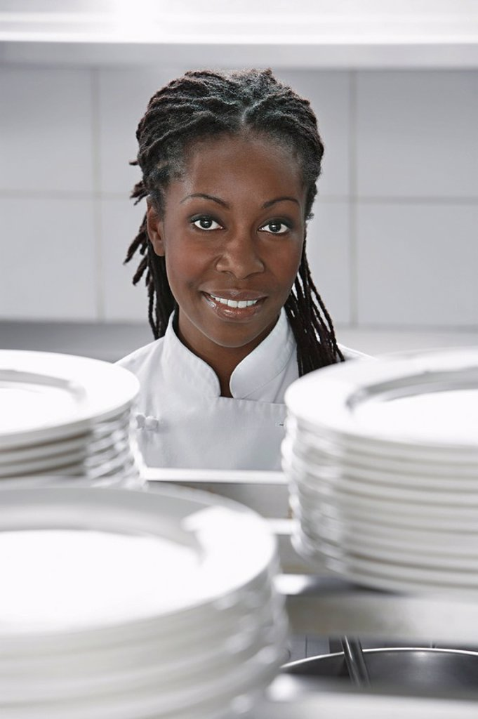 Female chef near stacked plates in kitchen portrait : Stock Photo