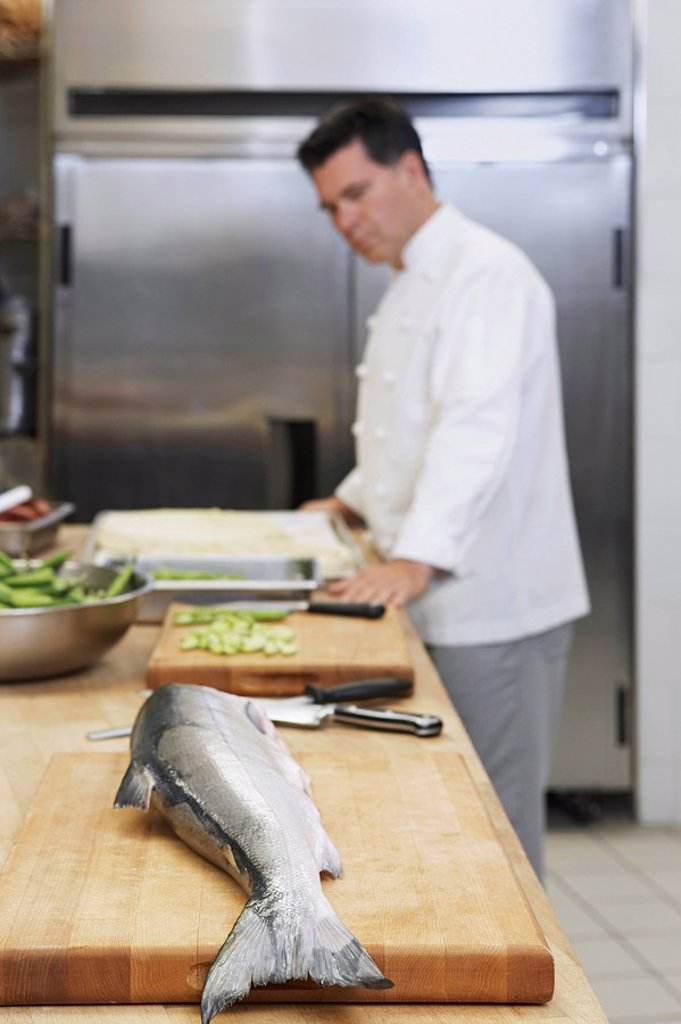Male chef in kitchen focus on salmon in foreground : Stock Photo