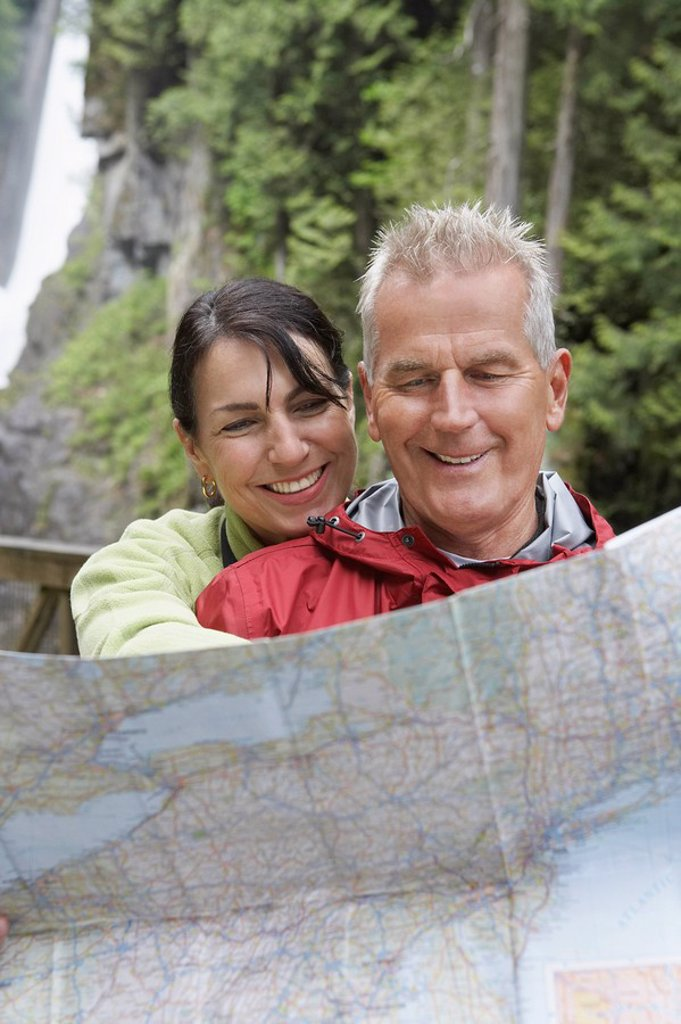 Stock Photo: 1654R-21054 Man and woman reading map waterfall in background