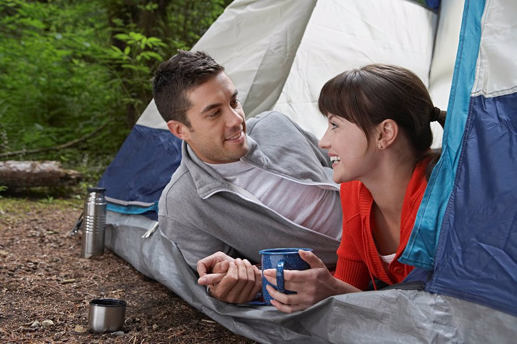 Couple with drinks lying in tent entrance : Stock Photo