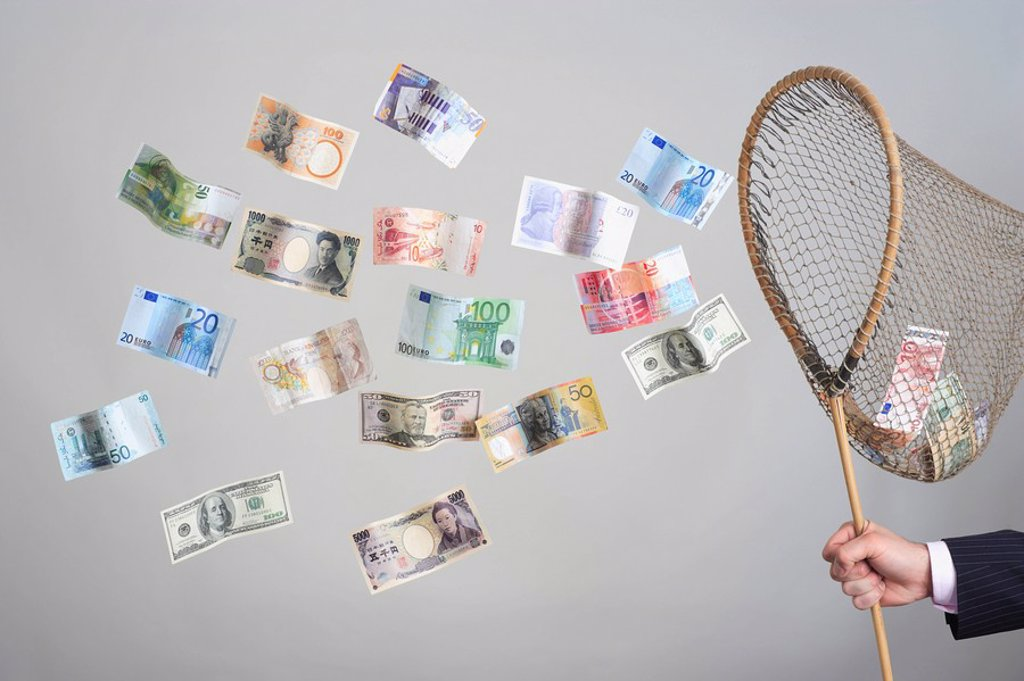 Man´s hand holding butterfly net catching flying banknotes : Stock Photo
