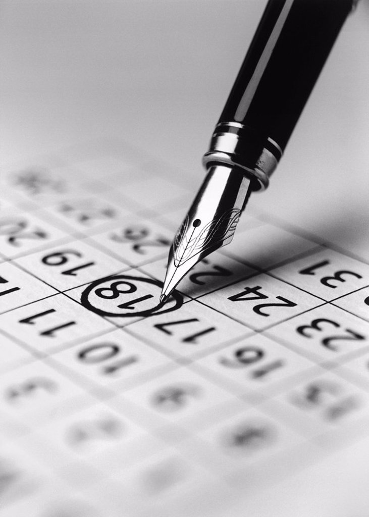 Stock Photo: 1654R-21928 Tip of fountain pen marking date in calendar b&w close_up