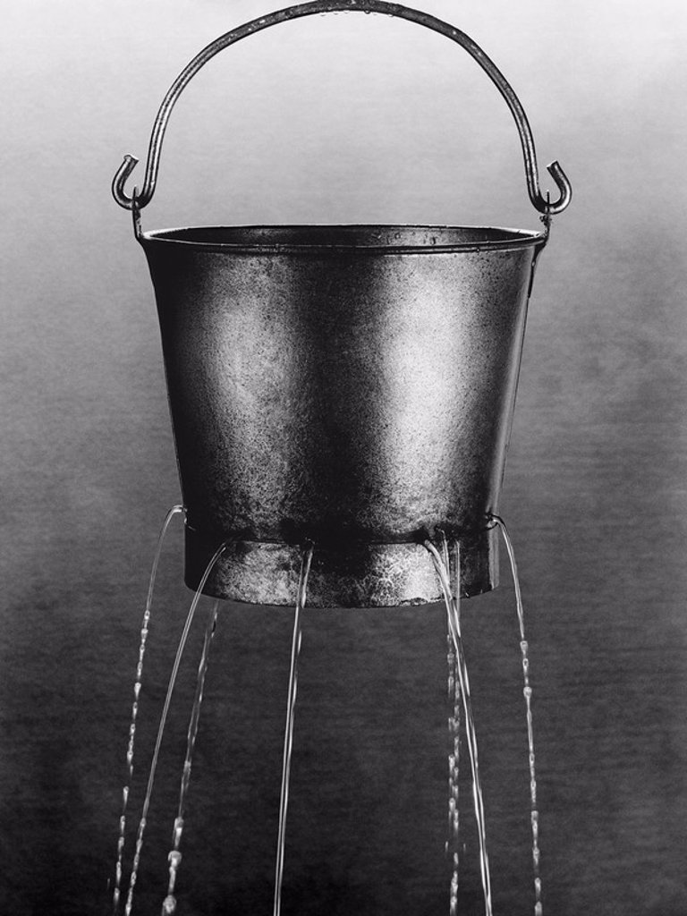 Stock Photo: 1654R-21929 Water poring through holes in bucket b&w
