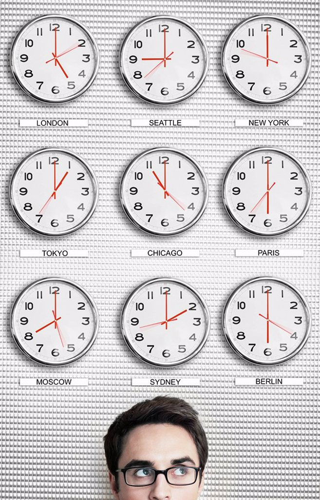 Stock Photo: 1654R-21960 Office worker in front of clocks showing time across the world