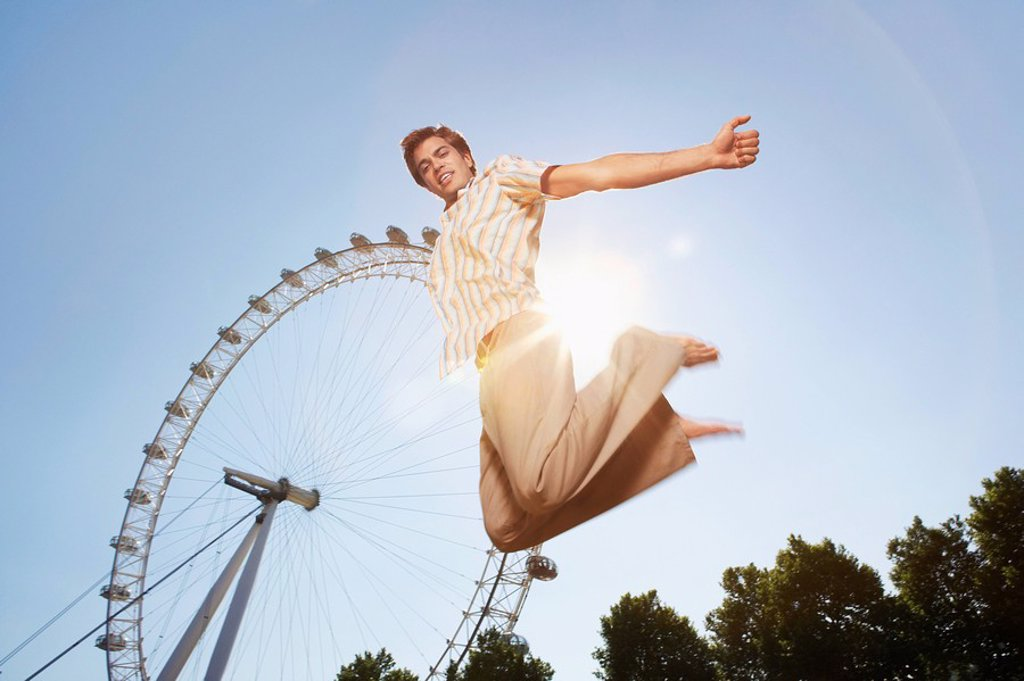 Young man in park jumping in front of London Eye portrait low angle view : Stock Photo