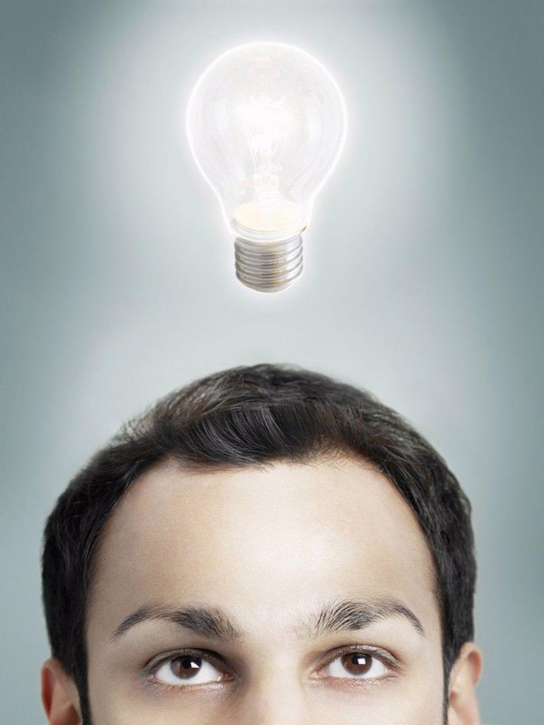 Illuminated lightbulb over man´s head high section studio shot : Stock Photo