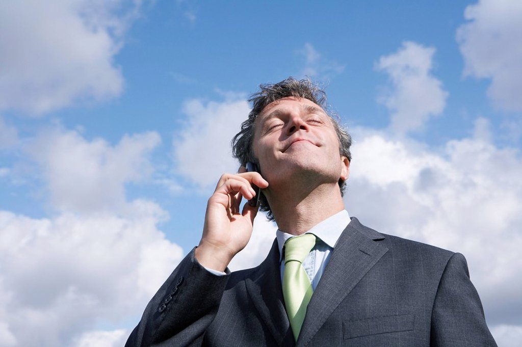 Business man talking on mobile phone smiling sky in background : Stock Photo