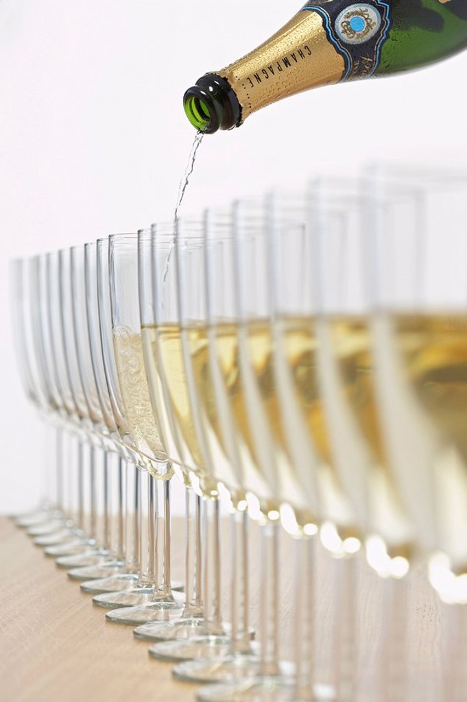 Stock Photo: 1654R-24079 Bottle of champagne filling row of glasses selective focus